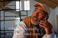 Picture of a man with a beard looking up while in a new construction site and he is talking on his cell phone